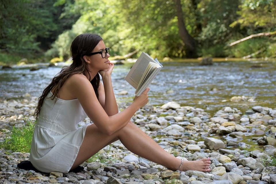 Jovem moça lendo um livro na beira de um córrego | Foto Pixabay