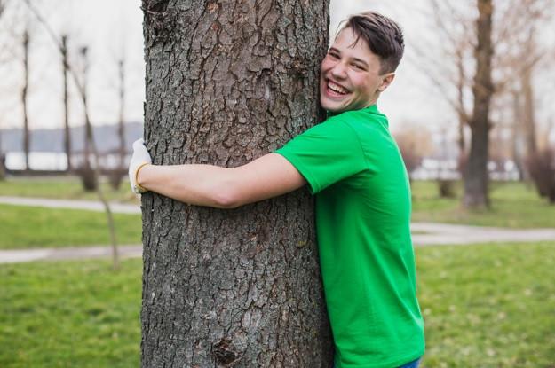 Jovem feliz abraçando uma árvore | Foto FreePik