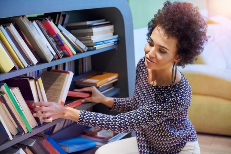 Mulher jovem organizando sua estante de livros para bons estudos | Foto Freepik