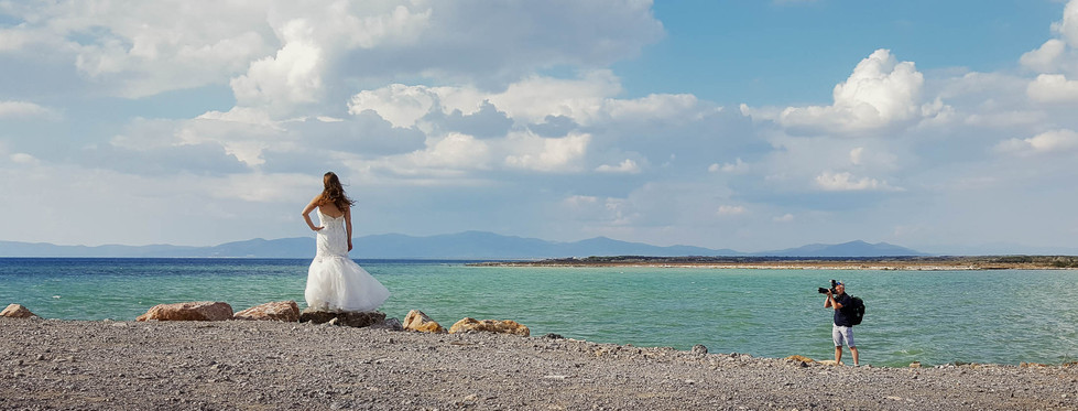 Wedding session - bride dressed with wedding dress at the sea with photographer at work