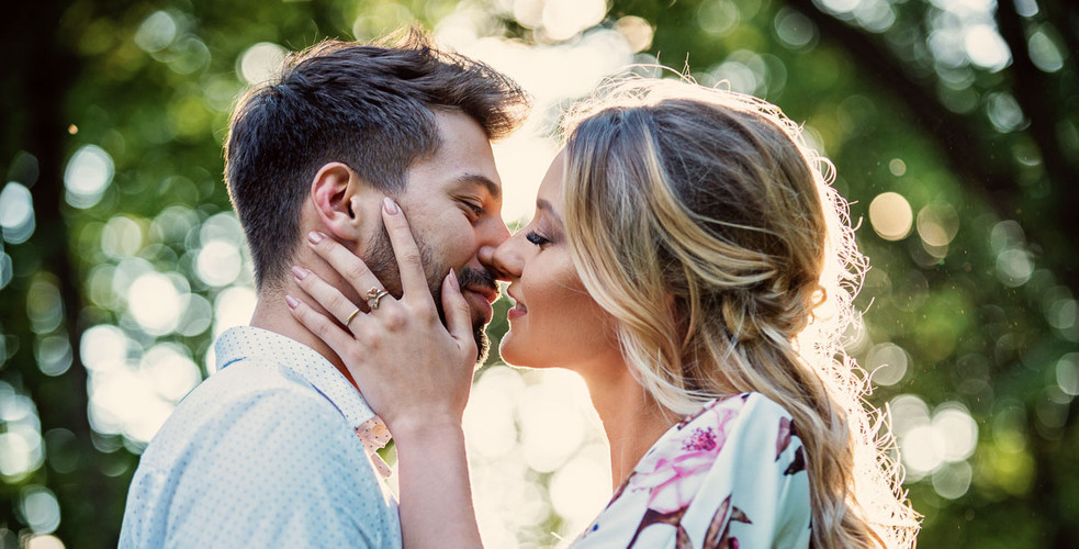 Portrait of engeged couple, kissing, embracing, smiling lit by the sun
