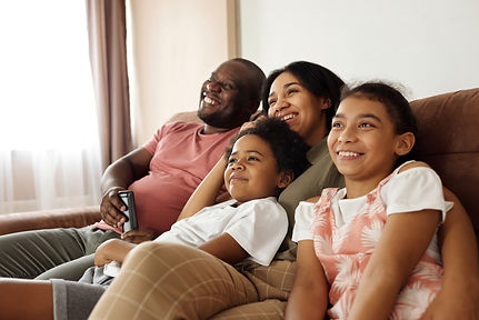 happy-family-sitting-on-a-couch-and-watc