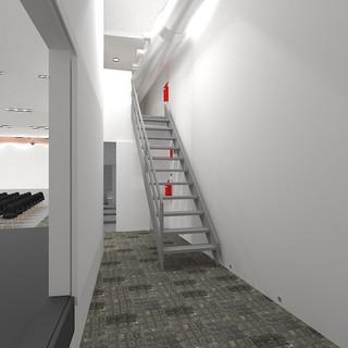 Vista escaleras a nuestro control técnico, con puerta corredera al lateral escenario abierta, con sillas montadas. Debajo de la escalera se ve la puerta entrada baños unisex.