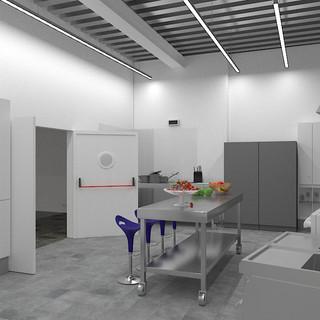 Vista cocina industrial completa (plancha, horno, fuegos, freidora, pila, lavavajillas, campana, frigorífico y congelador. Con puerta de acceso a Sala Refectorio.