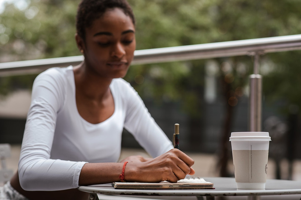 Woman writing at an outdoor cafe