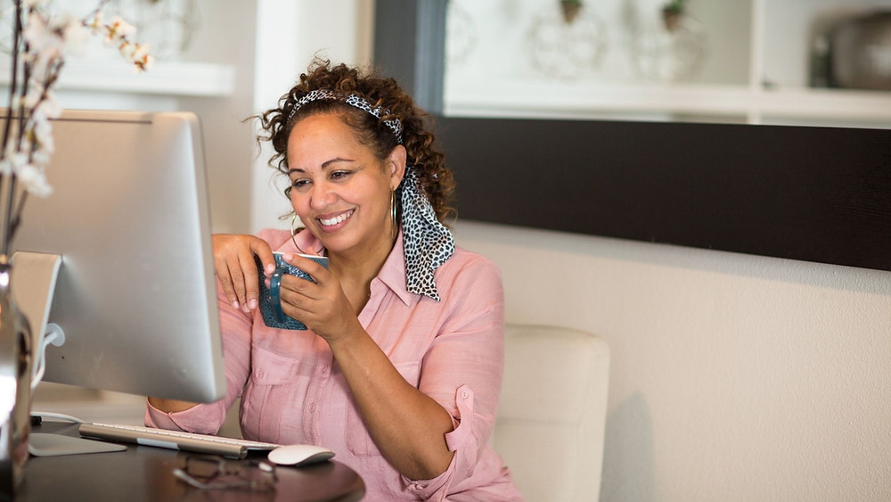 Beautiful mature lady smiling at her laptop