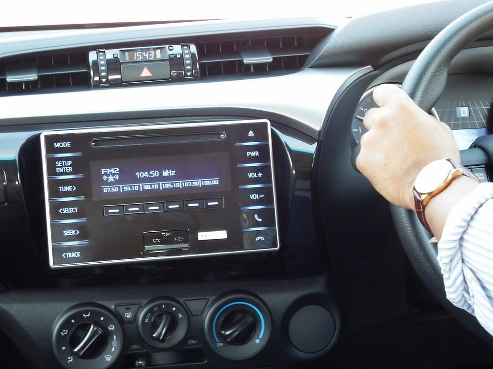 צילום של רדיו ברכב והנהגת מקשיבה