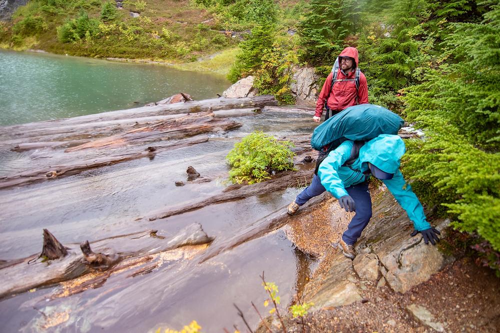 Hikers navigating a log jam on Upper Watson Lake