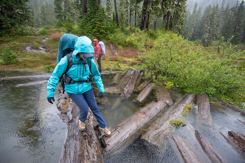 A hiker tests the strength of a floating log to hold her weight