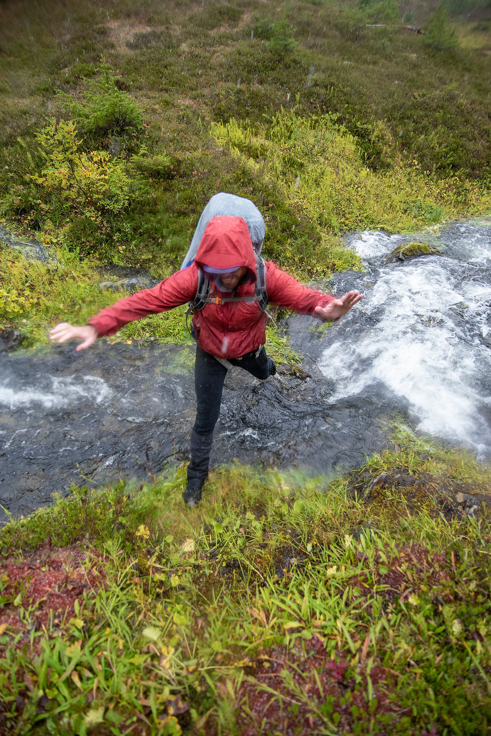 A hiker leaps across a stream