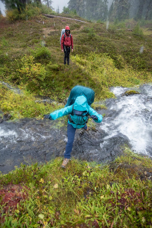 A hiker leaps across a running stream