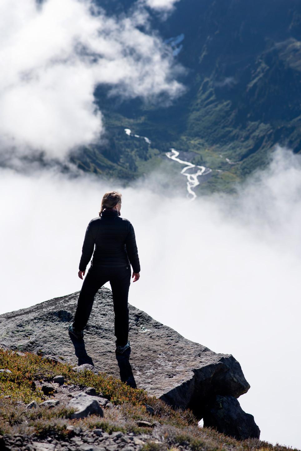 Megan on rock precipice with valley below