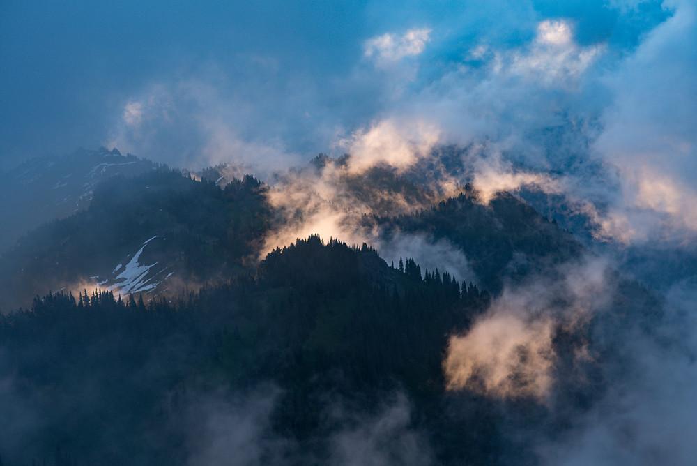 The sunrise illuminating the fog rising up from mountain peaks