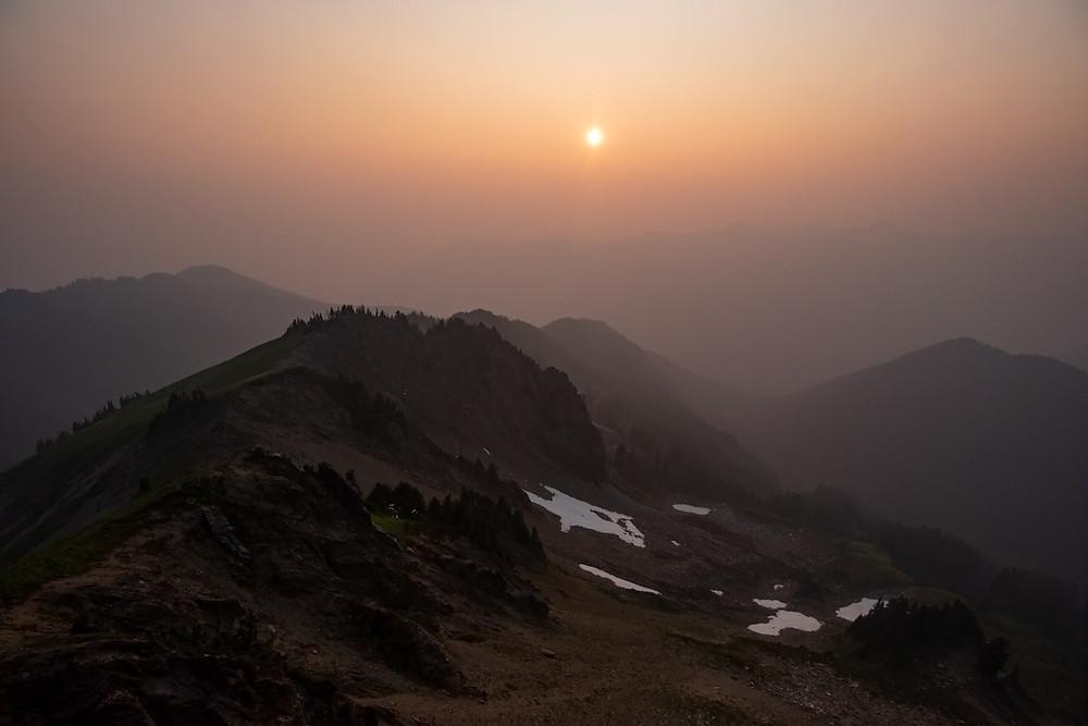 Hazy smoke filled sunset green mountain