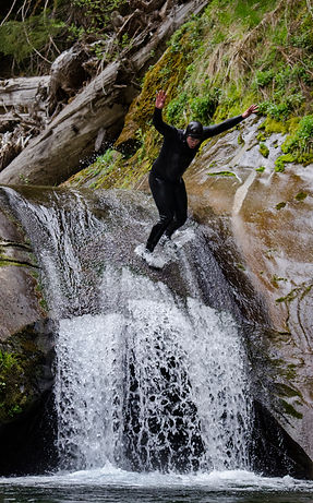 man in wet suit riding waterfall