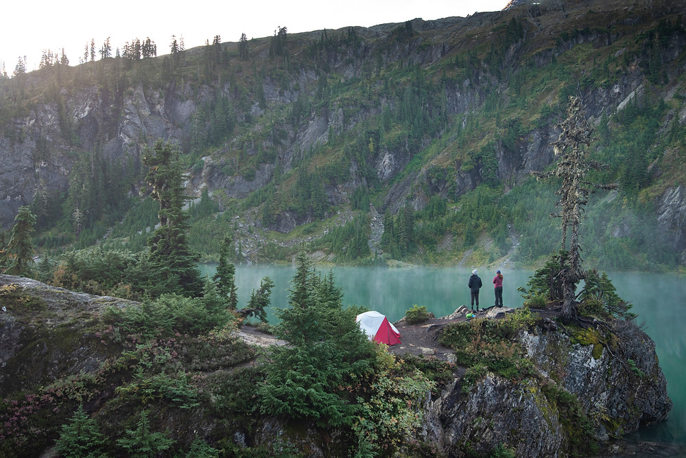 Two hikers watch the sunrise come up over Upper Watson Lake