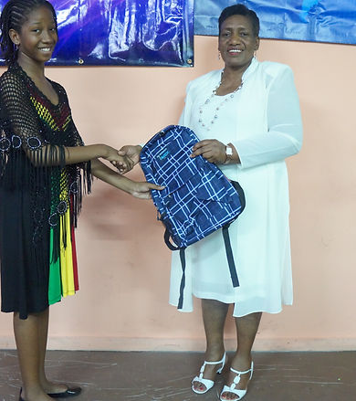 Founder/president Reverend Valerie giving a backpack to a teen in an outreach event in Jamaica.