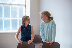 two child actors in the rehearsal room sharing a funny moment