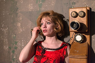 Actress on telephone on stage in theatre production