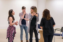 a group of three actors and a director in the rehearsal room for a musical theatre show