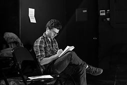 a theatre producer sits making notes in a black theatre space