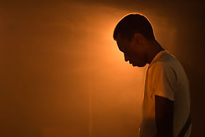 It Is So Ordered production at The Pleasance theatre, an actor stands silhouetted in orange light