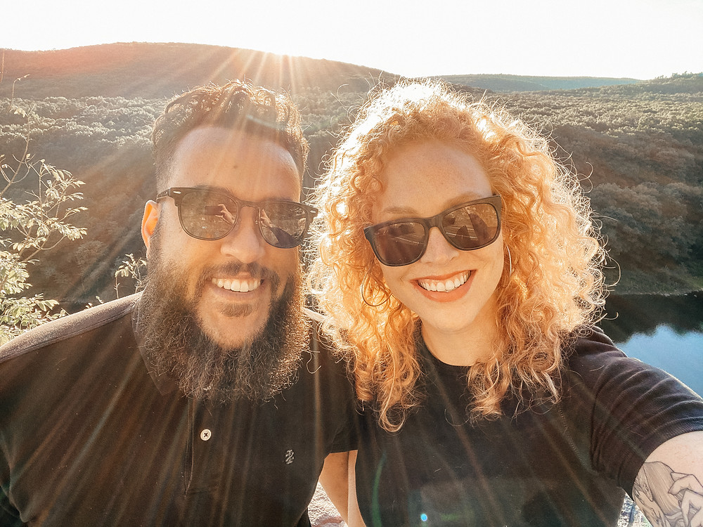 Black man and white woman smiling into camera on a mountaintop wearing sunglasses