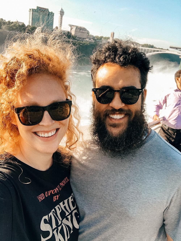 man and woman standing to take a selfie before Niagara Falls
