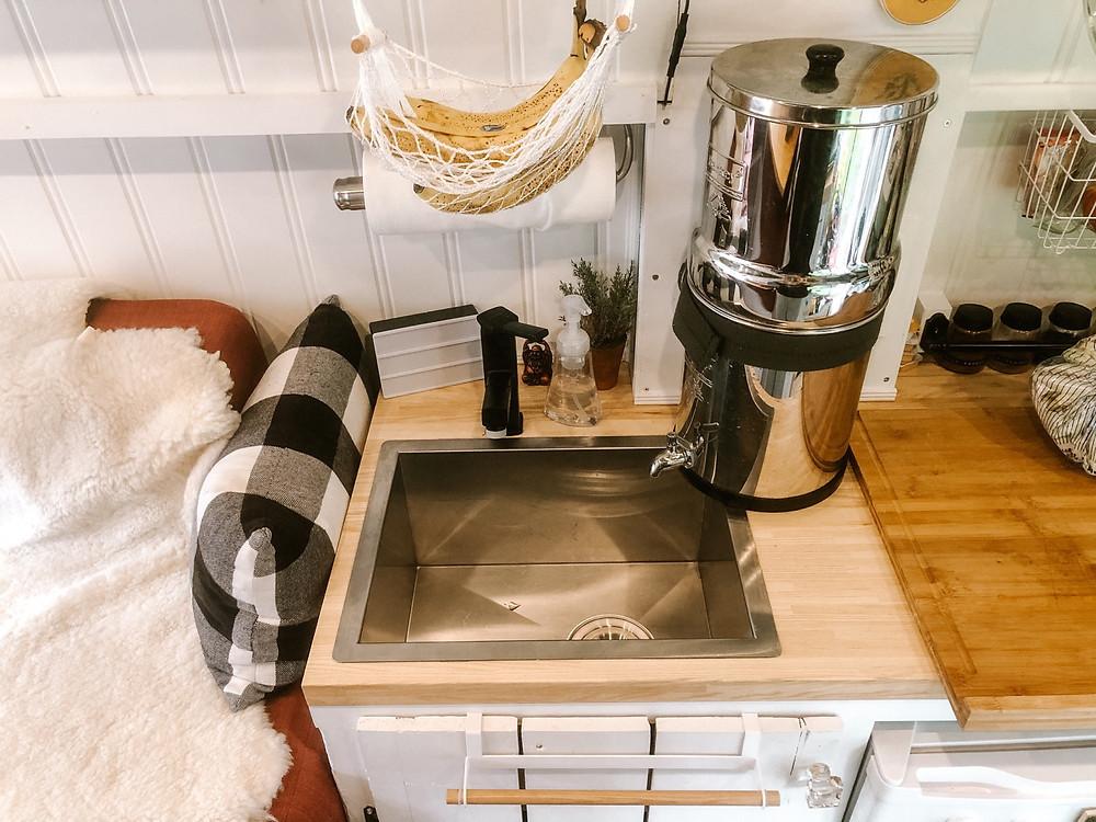 Stainless steel sink in wood countertop in a van