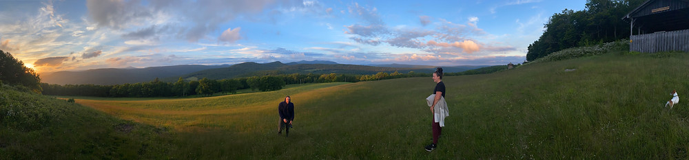 Panorama shot of a sunset in the Catskills with two people and a dog