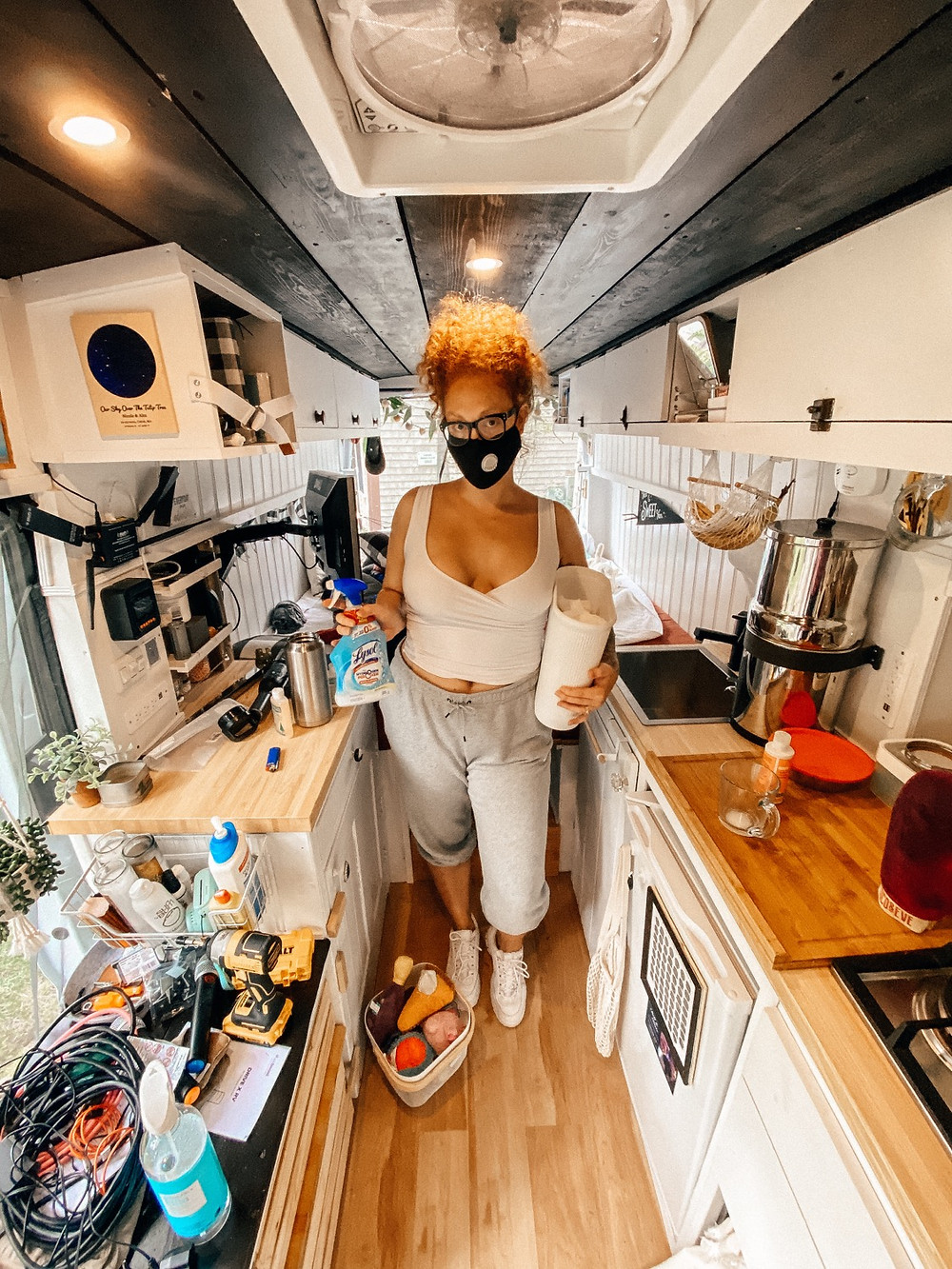 Woman in mask holding cleaner and full trashcan in camper van
