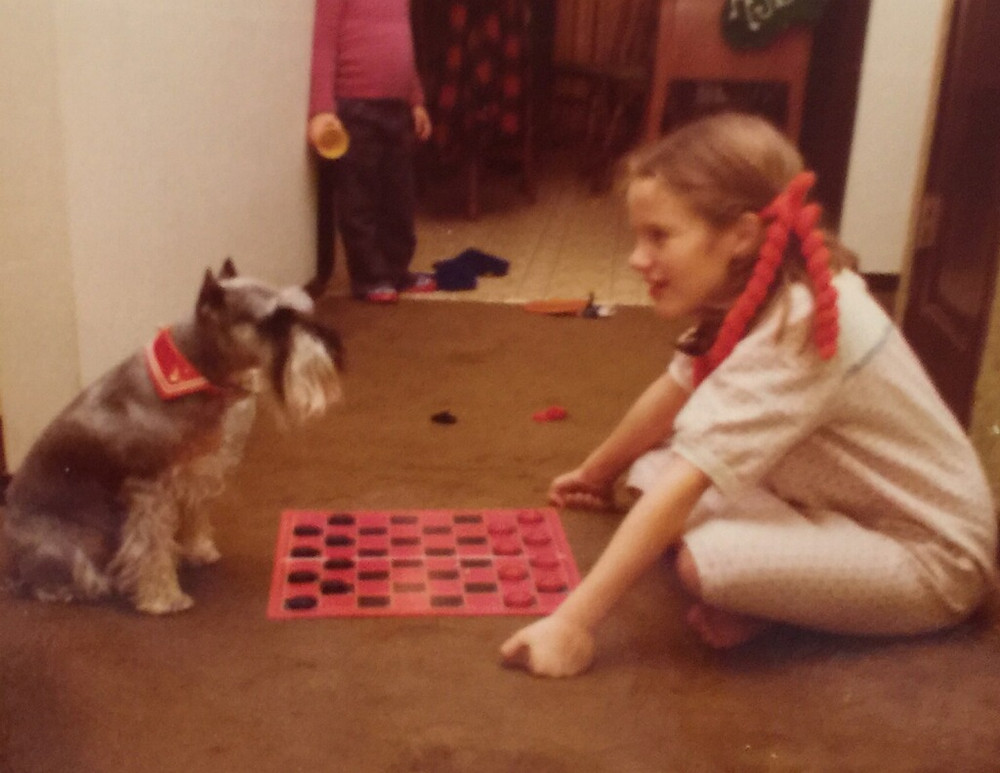 Dog playing checkers with girl