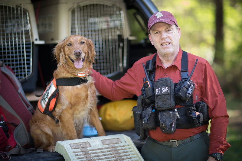"""Robert """"Bob"""" Calkins and K9 Ruger on back of truck ready to work"""
