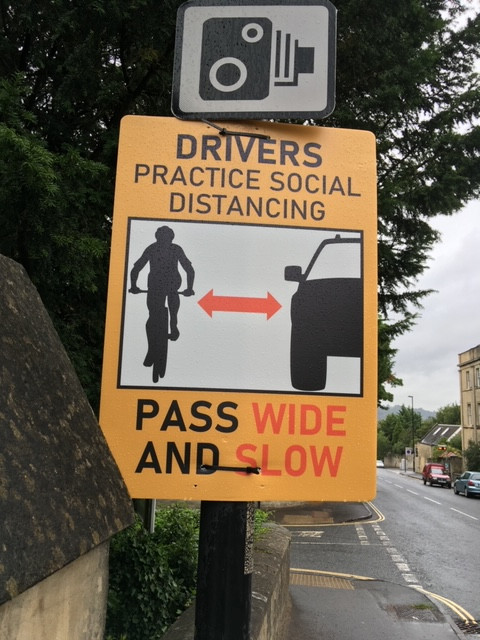 poster  on road telling drivers to pass wide and slow