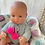 Thumbnail: Boneca com casaco e tapa-fraldas  cinza com pompons rosa neon