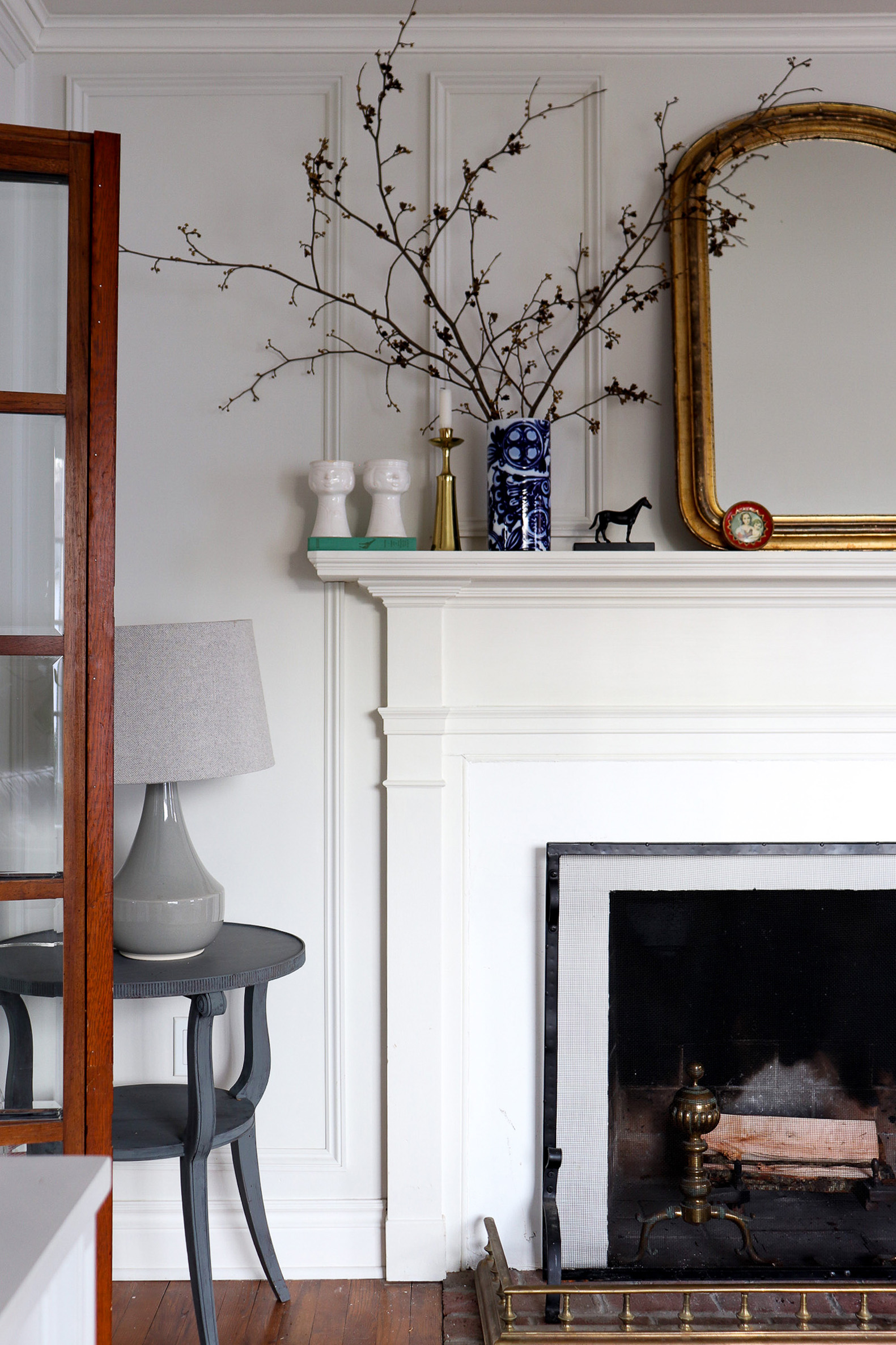 white fireplace with gold mirror and bra