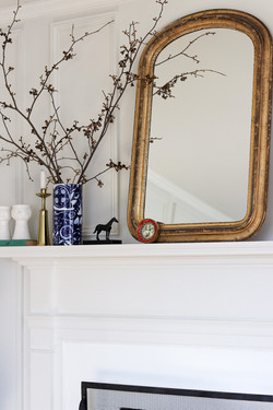gold louis mirror over fireplace