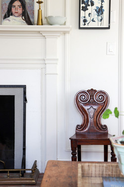antique hall chair next to fireplace