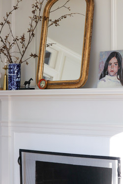 white fireplace with gold louis mirror