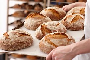Pães com casca crocante em bandeja com farinha