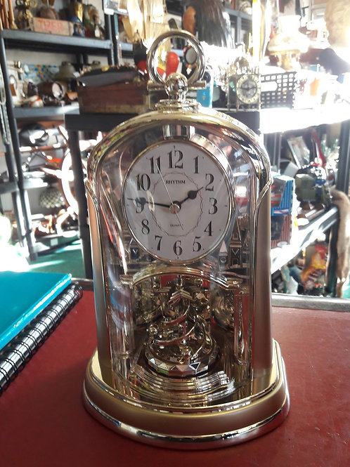 Rhythm gold tones rotating pendulum mantle clock.