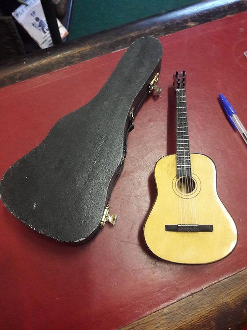 Miniature wind up musical guitar.