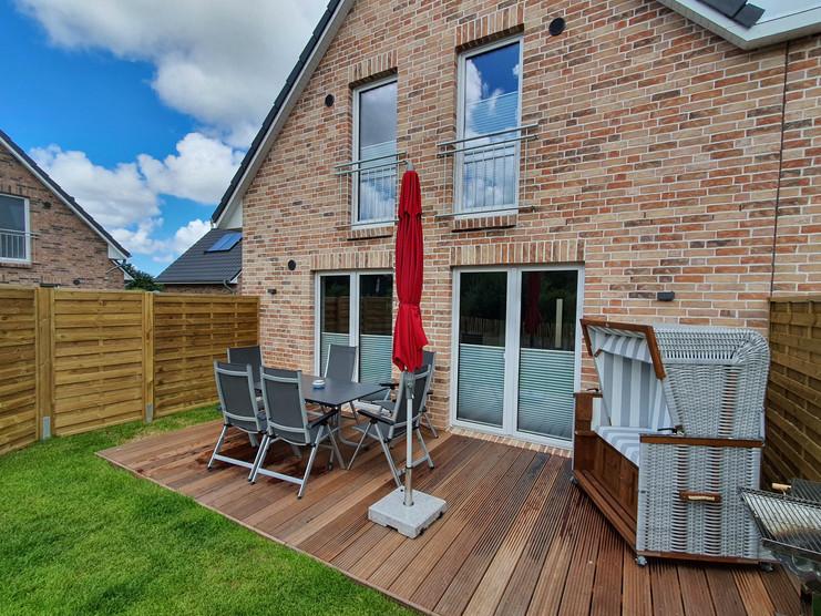 Ferienhaus Joe - Terrassenansicht  Holzterrasse mit Tisch, Stühlen, Strandkorb und Holzkohlegrill