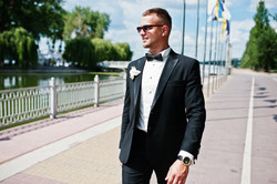 Elegant Groom On Sunglasses Walking Waterfront Of Lake With Flag Mock Up At Sunny Wedding Day.