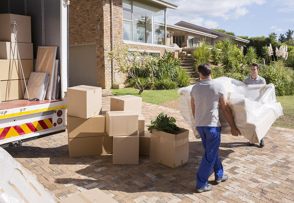 2 removal men carrying a large sofa to a house