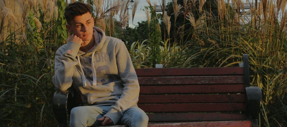 Young man sitting on outdoor bench at sunset.jpg