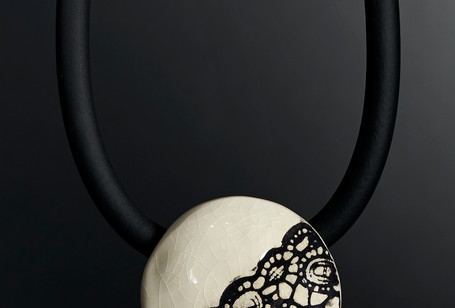 Collier tour de cou  Galet (diam 5cm environ) Grès blanc émaillé, décor dentelle engobe noir