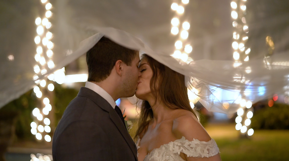 Couple kisses on their wedding day during nights of lights