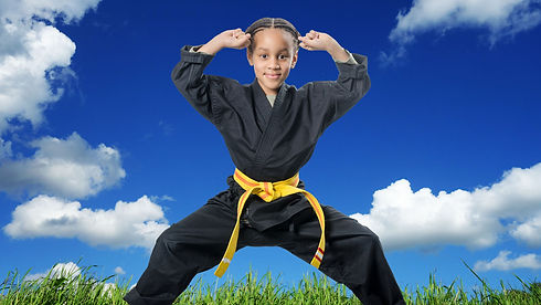 A young girl outside in a martial arts uniform