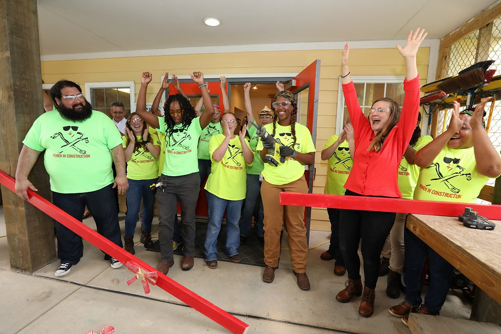 "Staff and graduates of the Women in Construction program at Moore Community House celebrate after the ceremonial ""ribbon"" was cut with a saw at the organization's expansion celebration. Photo by James Edward Bates"